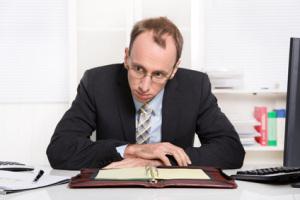 Mann sitzt unzufrieden am Schreibtisch und denkt nach