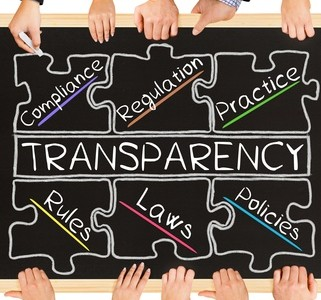 Photo of business hands holding blackboard and writing TRANSPARENCY concept