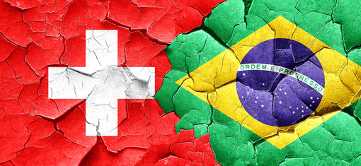 switzerland flag with Brazil flag on a grunge cracked wall